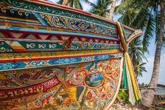 Beautiful Kolae boat, traditional Thai-Malayu fishing boat. Colorful mural painting and color cloth hanging on the bow of the boat. Coconut trees and local royalty free stock photography
