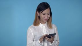 Beautiful korean female scrolling mobile. Young asian woman using smartphone for app or social media on blue background in studio. attractive millennial girl stock video footage