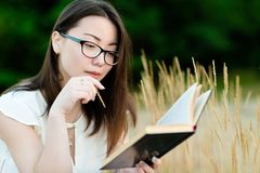 Beautiful korean girl reading book outdoors stock photography