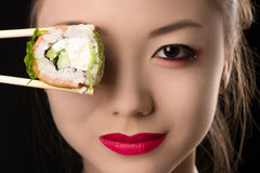 Beautiful Korean girl with roll instead eyes. Isolated on black background Stock Images