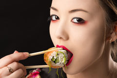 Beautiful korean teenager girl with bright makeup eating sushi. Isolated on black background Stock Photo
