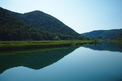 The beautiful Krka river water with a reflection of mountains. At Skradin, Croatia royalty free stock photography