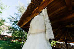 Beautiful lace top of wedding dress hanging on the wooden arbor. Outdoors royalty free stock photos