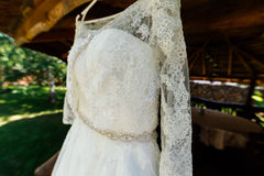 Beautiful lace top of wedding dress hanging on the wooden arbor. Outdoors stock photos