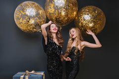 Beautiful ladies dancing with hands up in front of shining helium balloons and smiling. Indoor photo of refined brown. Haired birthday girl chilling with friend royalty free stock photos