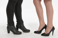 Beautiful ladies footwear: boots and pumps. The legs of two beautiful young ladies, one wearing long, leather boots, and the other wearing classy pumps. on white stock photography