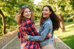 Beautiful ladies students walking in the park looking camera. stock photography