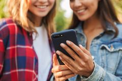 Beautiful ladies students walking in the park using mobile phone. royalty free stock images