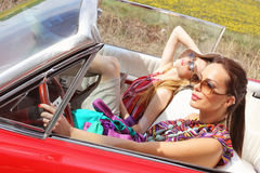 Beautiful ladies with sun glasses posing in a vintage car in a sunny day spring summer Royalty Free Stock Photos