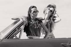 Beautiful ladies with sun glasses posing in a vintage car in a sunny day spring summer Royalty Free Stock Images