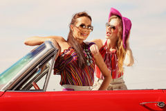 Beautiful ladies with sun glasses posing in a vintage car in a sunny day spring summer Stock Photos