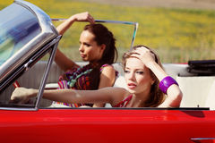 Beautiful ladies with sun glasses posing in a vintage car in a sunny day spring summer Stock Photo