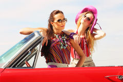 Beautiful ladies with sun glasses posing in a vintage retro car Royalty Free Stock Image