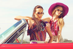 Beautiful ladies with sun glasses posing in a vintage retro car Royalty Free Stock Photo