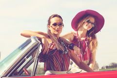 Beautiful ladies with sun glasses posing in a vintage retro car Stock Images