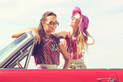 Beautiful ladies with sun glasses posing in a vintage retro car Stock Image