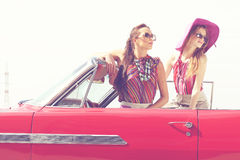 Beautiful ladies with sun glasses posing in a vintage retro car Stock Photos