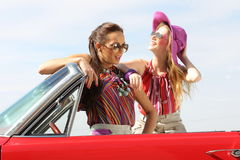 Beautiful ladies with sun glasses posing in a vintage retro car Stock Photography