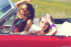 Beautiful ladies with sun glasses riding a vintage retro car Royalty Free Stock Photography