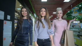 Beautiful ladies walking in a store with shopping bags. Slow motion. stock video footage