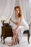 Beautiful lady. Beautiful redhead lady woman in white dress in vintage ambient looking for necklace stock photos