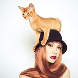 Beautiful lady with Abyssinian cat. Fashion photo of elegant lady with Abyssinian cat royalty free stock image