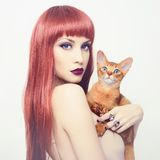 Beautiful lady with Abyssinian cat. Fashionable photo of elegant lady with Abyssinian cat stock image