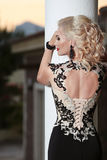 Beautiful lady back in elegant dress. Hairstyle. Red lips makeup Royalty Free Stock Image