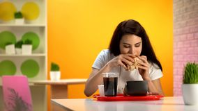 Beautiful lady biting tasty cheeseburger, sweet soda beverage standing on table. Stock photo royalty free stock photo