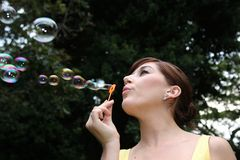 Beautiful Lady Blowing Bubbles Royalty Free Stock Photography