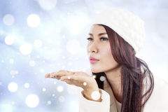 Beautiful lady blowing snowflakes on blue lights. Beautiful young lady blowing snowflakes on blue defocused lights background Royalty Free Stock Image
