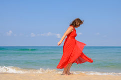 Beautiful lady in bright  elegant red dress  at beach Stock Photo