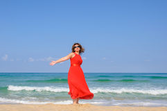Beautiful lady in bright  elegant red dress  at beach Royalty Free Stock Photos