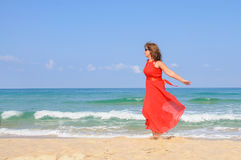 Beautiful lady in bright  elegant red dress  at beach Stock Image