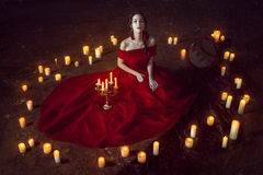 Beautiful lady with candles. Beautiful lady dressed in red ball gown sitting with candles royalty free stock images