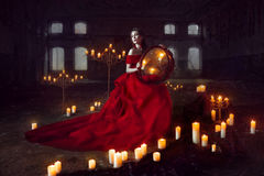 Beautiful lady with candles. Beautiful lady dressed in red ball gown sitting with candles Royalty Free Stock Image