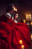 Beautiful lady with candles. Beautiful lady dressed in red ball gown sitting with candles Royalty Free Stock Photos
