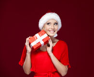 Beautiful lady in Christmas cap hands a present Stock Image