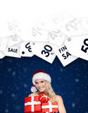 Beautiful lady in Christmas cap holds a set of gift Stock Photos
