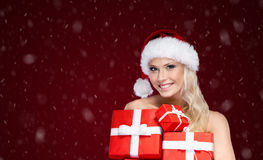 Beautiful lady in Christmas cap holds a set of presents Royalty Free Stock Images