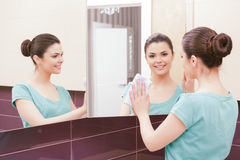 Beautiful lady cleaning mirror. From different angles. Pretty woman standing in front of mirror and wiping it with help of white cloth and having three royalty free stock image