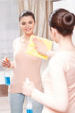 Beautiful lady cleaning mirror Royalty Free Stock Photo