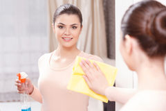 Beautiful lady cleaning mirror. Pureness of reflection. Young lady standing in front of mirror and wiping it with help of yellow cloth and special mean of stock photography