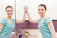Beautiful lady cleaning mirror. Total reflection. Young woman standing in front of mirror and wiping it with help of white cloth royalty free stock images