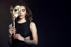 Beautiful lady with closed eyes hiding the half of her face behind the Venetian mask. Beautiful tattooed lady with dark wavy shining hair and perfect make-up Stock Photos
