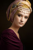 Beautiful lady with colored turban. Against a dark background Royalty Free Stock Photography