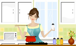 Beautiful lady cooking. In the kitchen Stock Photography