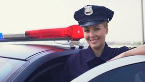 Beautiful lady cop in service cap smiling to camera, woman protecting city. Stock footage stock video