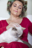 Beautiful lady with curlers stroking the cat Royalty Free Stock Image