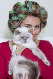 Beautiful lady with curlers stroking the cat Stock Photo